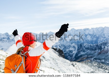 Happy Hiking Woman and Success in Winter Mountains, Arms Outstretched. Fitness and healthy lifestyle outdoors in snowy nature. Motivation Mountaineer Climber Top of Mountain Peak with Arms Raised. - stock photo