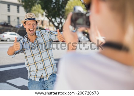 Happy hip man posing for his girlfriend on a sunny day in the city - stock photo