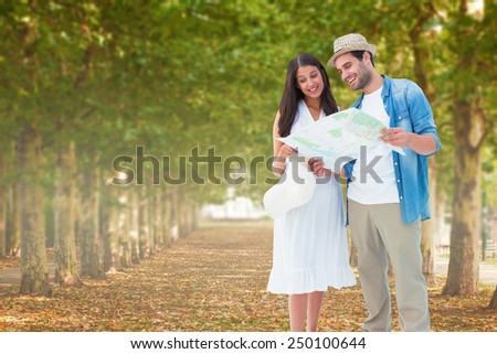 Happy hipster couple looking at map against walkway along lined trees in the park - stock photo