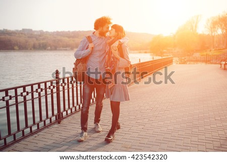 Happy hipster couple on holiday having fun and enjoy the time. Couple in love walking by the lake and talking, wearing modern clothes