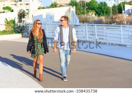 Happy hipster couple on holiday having fun and enjoy the time. Dating young best friend in love walking and talking wearing all season clothes. Beautiful multiracial tourist in city looking each other - stock photo