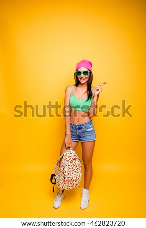 happy hipster girl with backpack and lollipop, standing yellow background