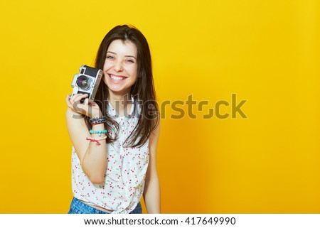 Happy hipster girl with retro camera in studio against yellow background with copy space - stock photo