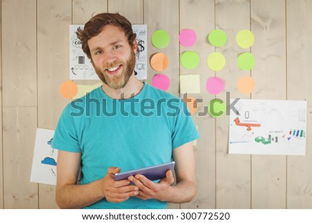 Happy hipster using his tablet pc in his office - stock photo