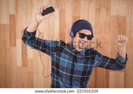 Happy hipster wearing headphones enjoying music against wooden wall - stock photo