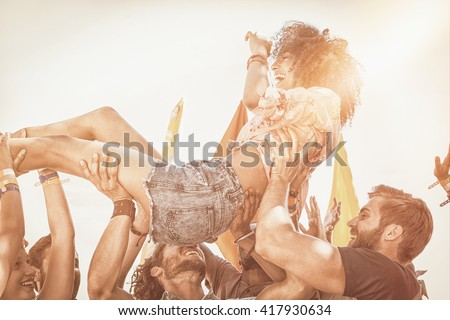 Happy hipster woman crowd surfing at a music festival - stock photo