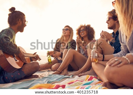Happy hipsters relaxing and playing guitar at the beach. Friends drinking beers and listening to music. Having fun at beach party in evening. - stock photo