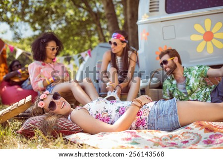 Happy hipsters relaxing on the campsite at a music festival - stock photo