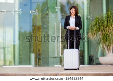 Happy Hispanic - Asian businesswoman at an airport carrying a suitcase - stock photo