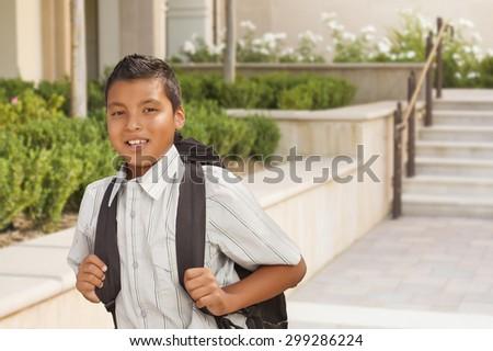 Happy Hispanic Boy with Backpack Walking on School Campus. - stock photo
