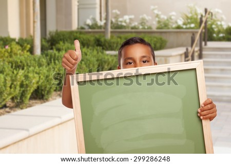 Happy Hispanic Boy with Thumbs Up Holding Blank Chalk Board Outside on School Campus. - stock photo