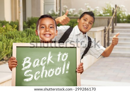 Happy Hispanic Boys Giving Thumbs Up Holding Back to School Chalk Board Outside on School Campus. - stock photo
