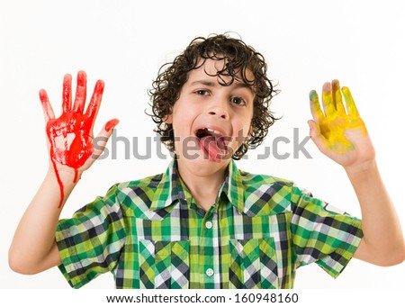 Happy Hispanic child gesturing at the camera with his two hands painted. Watercolor mess at home. Not a funny way to have fun. Kid enjoying his free time playing with watercolor paint. - stock photo