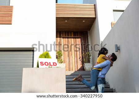 Happy Hispanic couple hugging in front of new house - stock photo