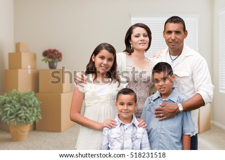 Happy Hispanic Family in Empty Room with Packed Moving Boxes and Potted Plants.