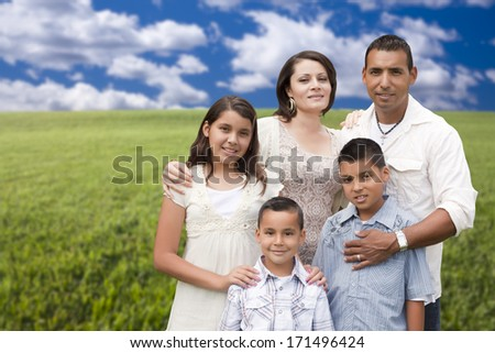 Happy Hispanic Family Portrait Standing in Grass Field.