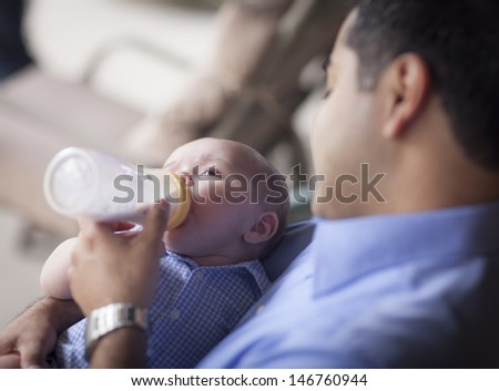Happy Hispanic Father Bottle Feeding His Very Content Mixed Race Son. - stock photo