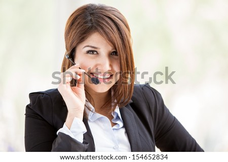 Happy Hispanic female call center representative wearing a suit and a headset and taking a customer service call