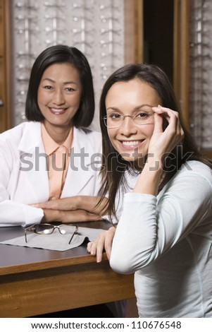 Happy hispanic female patient and optometrist