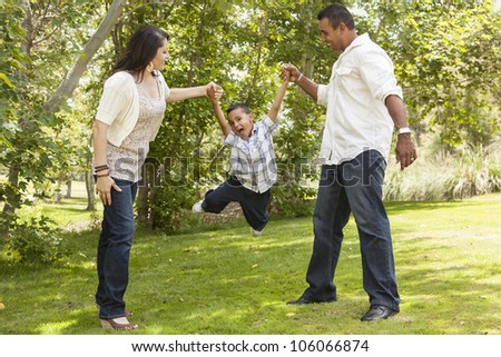 Happy Hispanic Mother and Father Swinging Son in the Park. - stock photo
