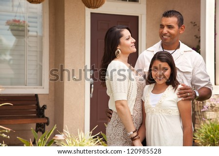 Happy Hispanic Mother, Father and Daughter in Front of Their Home.