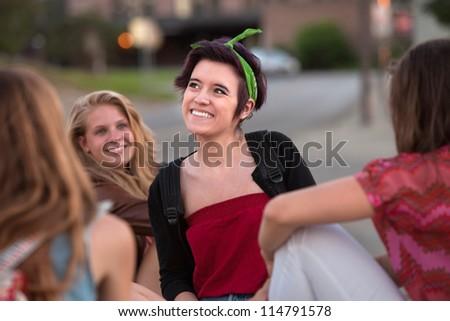 Happy Hispanic teenage girl with friends looking away - stock photo