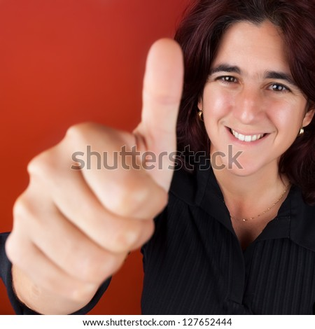 Happy hispanic woman in her thirties doing the thumbs up sign on a bright red background - stock photo