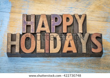 Happy Holidays banner or greeting card in vintage letterpress wood type blocks stained by color inks - stock photo