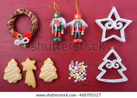 Happy Holidays Christmas background flat lay with ornaments on a red rustic wood background.