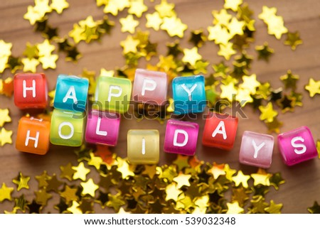 Happy Holidays. Colorful alphabet cubes with gold stars. Shallow depth of field.