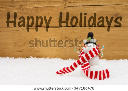 Happy Holidays Message, A Snowman on snow with a weathered wood background and text Happy Holidays - stock photo