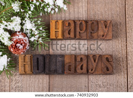 Happy holidays text on a wooden surface with snowy evergreen tree branch and pinecone