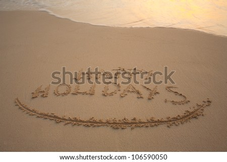happy holidays written in the sandy beach