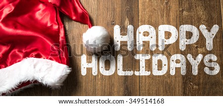 Happy Holidays written on wooden with Santa Hat - stock photo