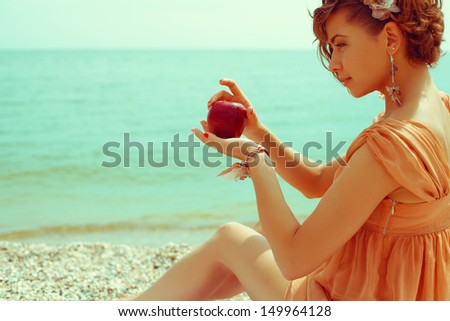 Happy honeymoon concept. Young girl in trendy vintage dress sitting on the beach and holding a red apple - love symbol. Sunny summer day. Copy-space. Outdoor shot