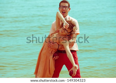 Happy honeymoon concept. Young happy married couple of hipsters in trendy clothes walking and playing on beach. Sunny summer day. Vintage (retro) style. Copy-space. Outdoor shot