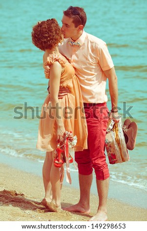 Happy honeymoon concept. Young married couple of hipsters standing together on the beach, kissing, holding their photocamera, suitcase and shoes. Sunny summer day. Vintage style. Outdoor shot