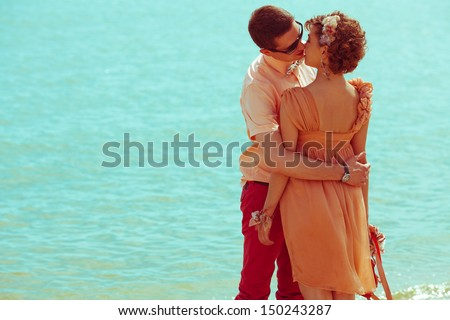 Happy honeymoon (vacation) concept. Young happy married hipsters in trendy clothes standing and kissing over blue ocean (sea) background. Sunny summer day. Copy-space. Outdoor shot