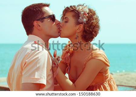 Happy honeymoon (vacation) concept. Young married couple of hipsters in trendy clothes kissing and hugging on the beach. Sunny summer day. Close up. Outdoor shot - stock photo