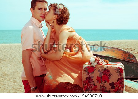 Happy honeymoon (vacation) concept. Young married couple of hipsters in trendy clothes kissing at the beach. Sunny summer day. Copy-space. Outdoor shot
