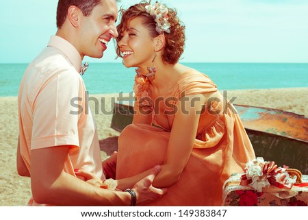 Happy honeymoon (vacation) concept. Young married couple of hipsters in trendy clothes playing and laughing on the beach. Sunny summer day. Copy-space. Outdoor shot