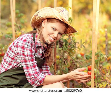 Happy horticulturist woman in straw hat in the backyard of the house. Young attractive Caucasian female gardener holding ripe vegetables. - stock photo