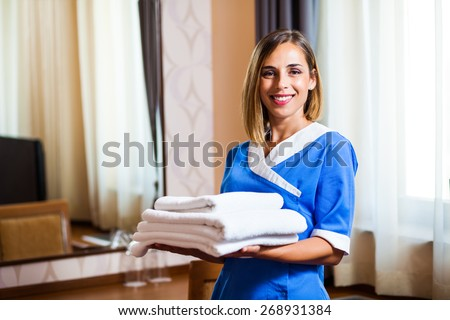 Happy hotel maid holding towels - stock photo