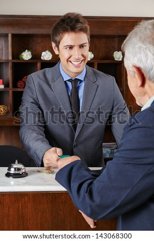 happy hotel receptionist giving key card to senior man - stock photo