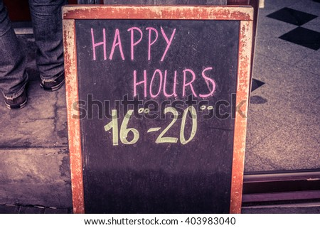 Happy hour board with text written in chalk - stock photo