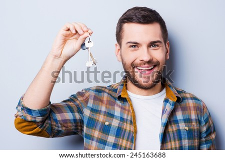 Happy house owner. Smiling young man holding keys and looking at camera while standing against grey background - stock photo