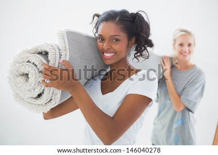 Happy housemates carrying rolled up rug looking at camera in new home - stock photo