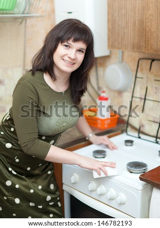 Happy housewife cleans the gas stove  with melamine sponge