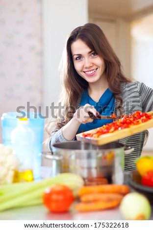 Happy  housewife cooking veggie lunch with vegetables in  kitchen  at home - stock photo