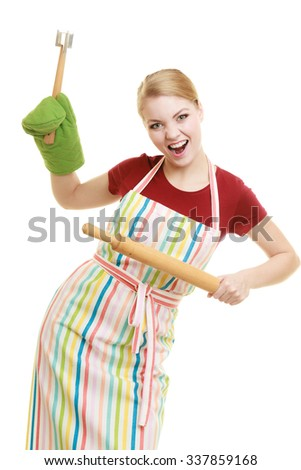 Happy housewife or baker chef wearing kitchen apron holds baking rolling pin meat hammer utensil isolated on white